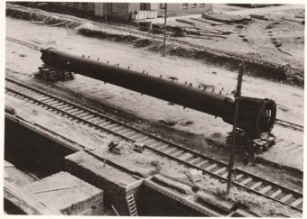 """Picture 1 shows a distillation column lying next to a railroad track. It is about 20 m long […]. Visible on the column are a large number of nozzles, to which piping will be attached later, after positioning, during assembly. In the background (center) is construction material in the form of planks and pipes."" '(Photo 1943/44, description by I.G. Farben defense counsel, Wollheim lawsuit, 1955)'© Central State Archive of Hesse (records of Wollheim lawsuit)"