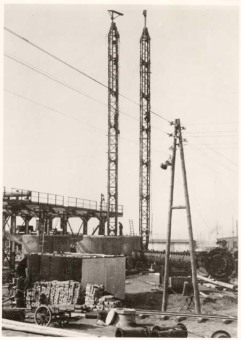 """In Picture 2, a column is lying at an angle in front of its concrete foudation, with the connection nozzles clearly visible. Two assembly towers have been positioned, with which the column is to be hoisted […] In the foreground of the picture, construction material in the form of stones is visible.""'(Photo 1943/44, description by I.G. Farben defense counsel, Wollheim lawsuit, 1955)'© Central State Archive of Hesse (records of Wollheim lawsuit)"