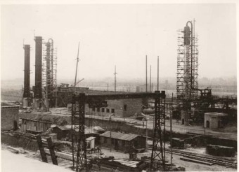 """Picture 3 shows, at left, three columns that have been positioned, with the assembly  towers already removed […] At right in the picture, a scaffolded column is visible, with a number of pipes already installed. The light-colored part, about 3/4 of the way up, is the insulation [...] About 1 m above the planks of the actual work platforms, handrails have been attached so that work can be done on these platforms without belts, but in an accident-proof way.""'(Photo 1943/44, description by I.G. Farben defense counsel, Wollheim lawsuit, 1955)'© Central State Archive of Hesse (records of Wollheim lawsuit)"