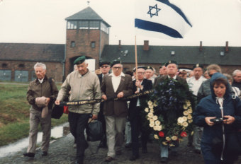Ya'acov Silberstein with members of his organization for support of Holocaust survivors; Silberstein is holding the Israeli flag, Auschwitz, 1975