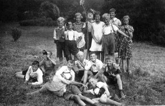 Group photo of children, taken around 1935/36, when Manfred Wolf was about 11. The girl in the center, wearing the white dress, is Clementine Scheit, a good friend. Manfred Wolf is the boy right below her, laughing into the camera.